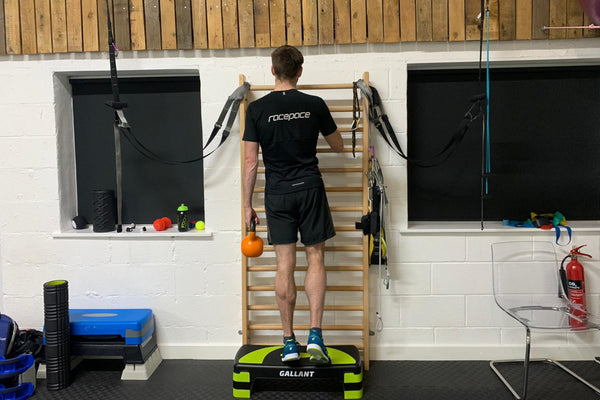 A male runner stood on the edge of a step doing weighted single leg calf raises holding an orange kettlebell
