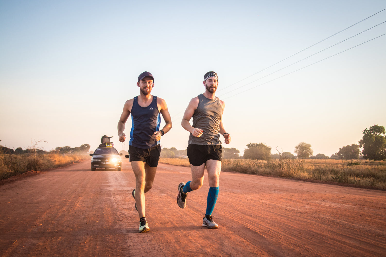 Two runners stride along a dirt road side by side