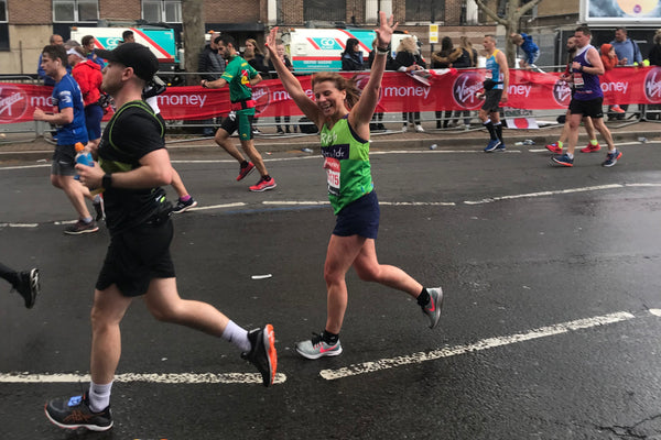 A female marathon runner waves to family whilst running past in the rain