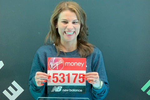 Ruth Bennett holds up her London Marathon bib number with a big smile on her face