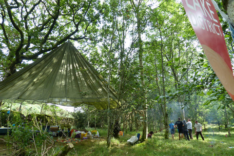 Woodland area with a canopy tent as people spend time in nature
