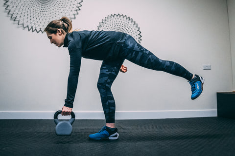 A lady performs a single leg dead lift with a kettlebell