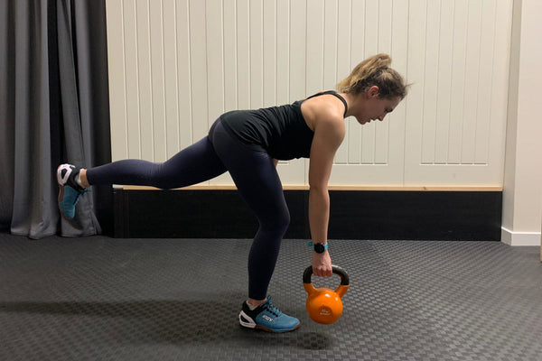 A female performs a weighted single leg deadlift with a kettlebell as a run strengthening exercise