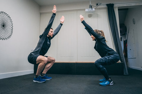 A male and female athlete holding a squat position facing each other during a strength training session for runners.