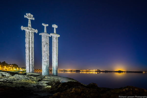 The impressive 'three swords' site at Stavanger, Norway at dusk with the glow of the town's lights in the background