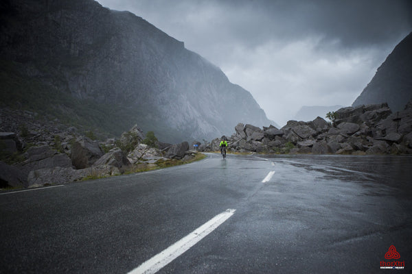 A lone cyclist rides through a misty and rocky mountain pass in Norway during the Thorxtri
