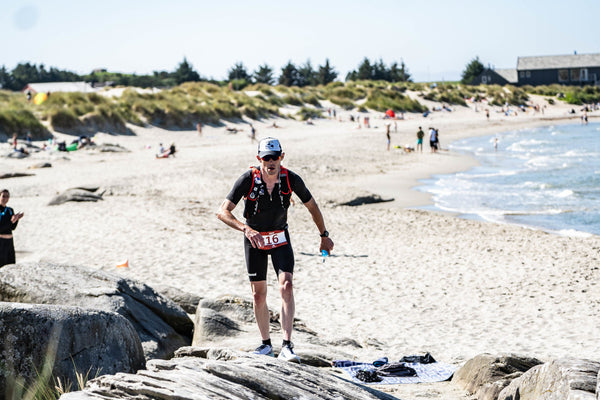 A runner battles over rocks and sand on the Norweigan coastline during the thorXtri extreme triathlon event