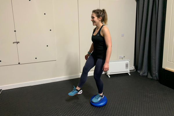 A female runner standing on one leg on a wobble cushion to improve balance and lower leg conditioning