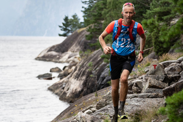 A male trail runner on a rocky path beside the Lysefjord in Norway
