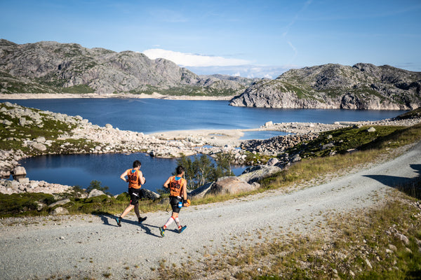 Two runners follow a wide open trail beside a small lake during the Rockman Swimrun event in Norway