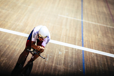 Aerodynamic cyclist on the wooden boards of a velodrome