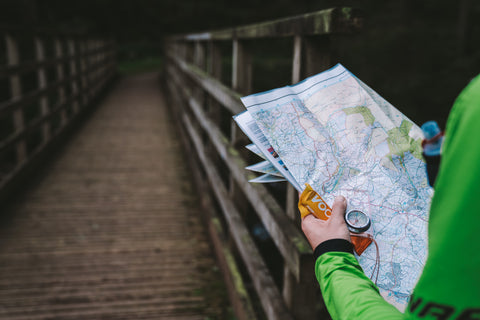 A runner route planning holding a compass and Voom energy bar, reading a map before heading across a wooden bridge