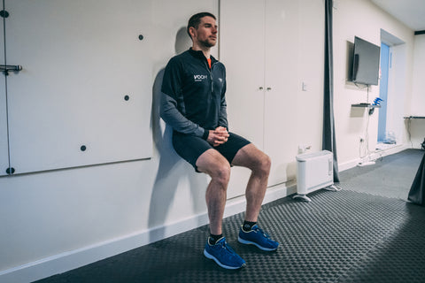 A man squats against a wall holding a wall sit position in the gym