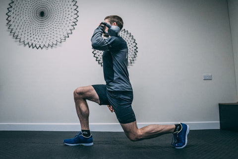 A male runner doing a lunge exercise holding a kettlebell in one hand