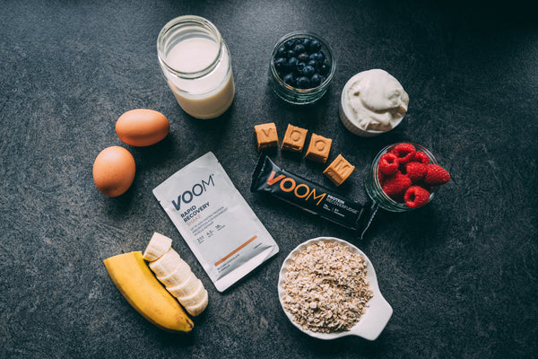 Ingredients for protein pancakes, including banana, oats, milk, eggs, berries and VOOM Rapid Recovery protein powder