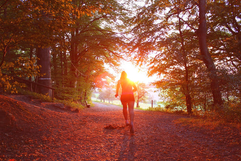 A female runner heading out of a forest into a brilliant orange and red sunset