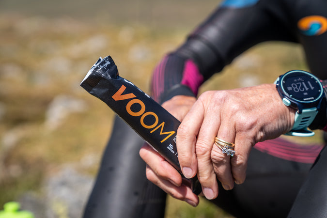Close up of someone in a wetsuit holding a Voom RecoverFudge bar after a swim session