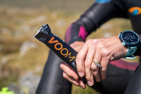 A person in a wetsuit sits enjoying a RecoverFudge protein bar post-workout.
