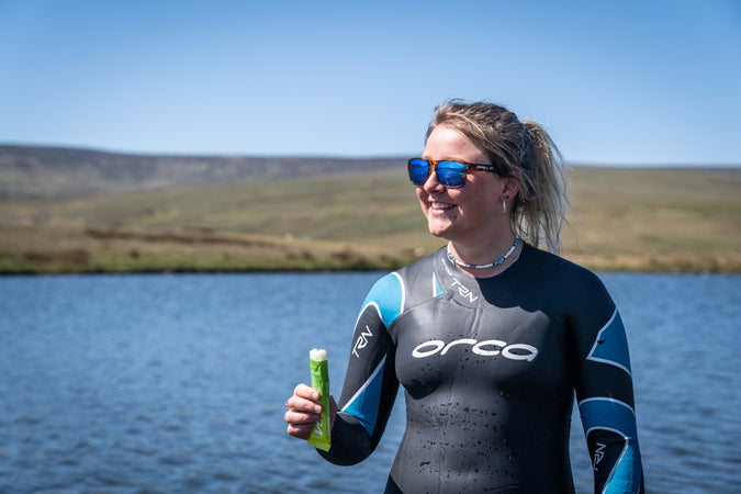 A woman in a wetsuit stood by a lake holding a half eaten Voom electro energy bar with a smile on her face.