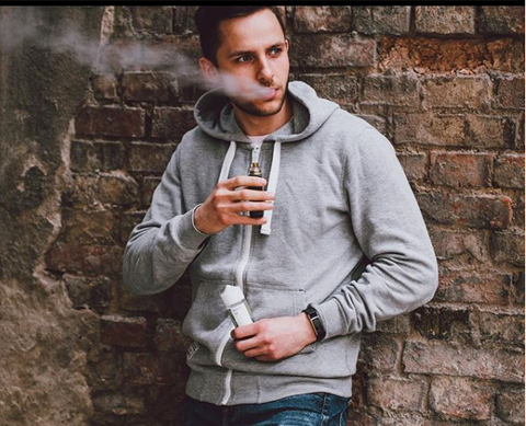 man standing in front of brick wall vaping