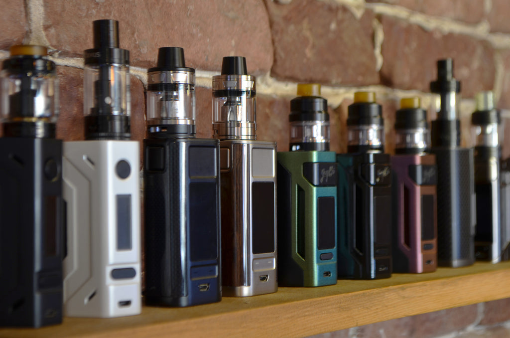 an array of vaping mods on a shelf against a brick wall