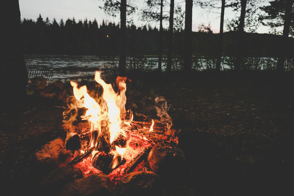 picture of a campfire near a river at sunset
