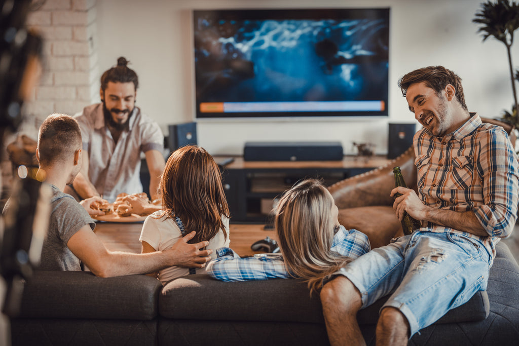 group of friends at a house party with tv on in background