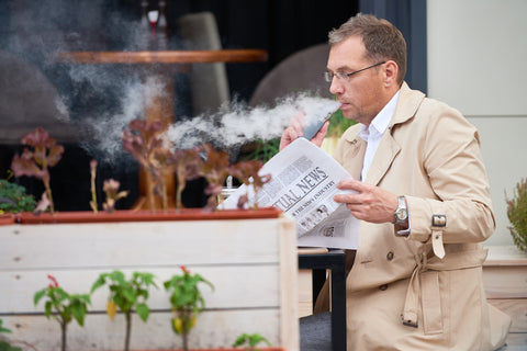 businessman sitting at cafe vaping and reading newspaper