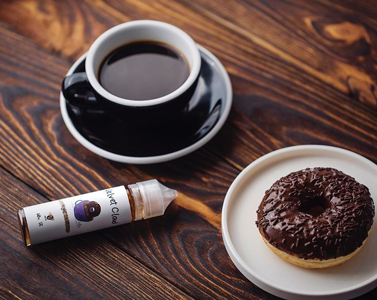a cup of coffee, a donut, and a bottle of premium Velvet Cloud e-liquid