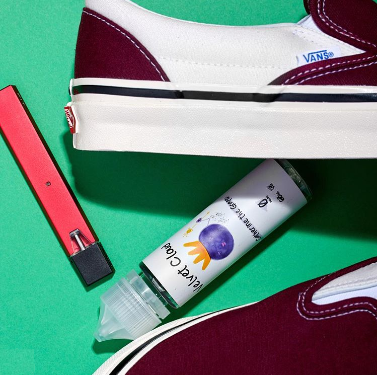 bottle of grape-flavored e-juice between a pair of red and white shoes