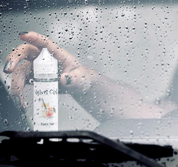 woman reaching for a bottle of peach flavored Velvet Cloud e-liquid on a rainy day