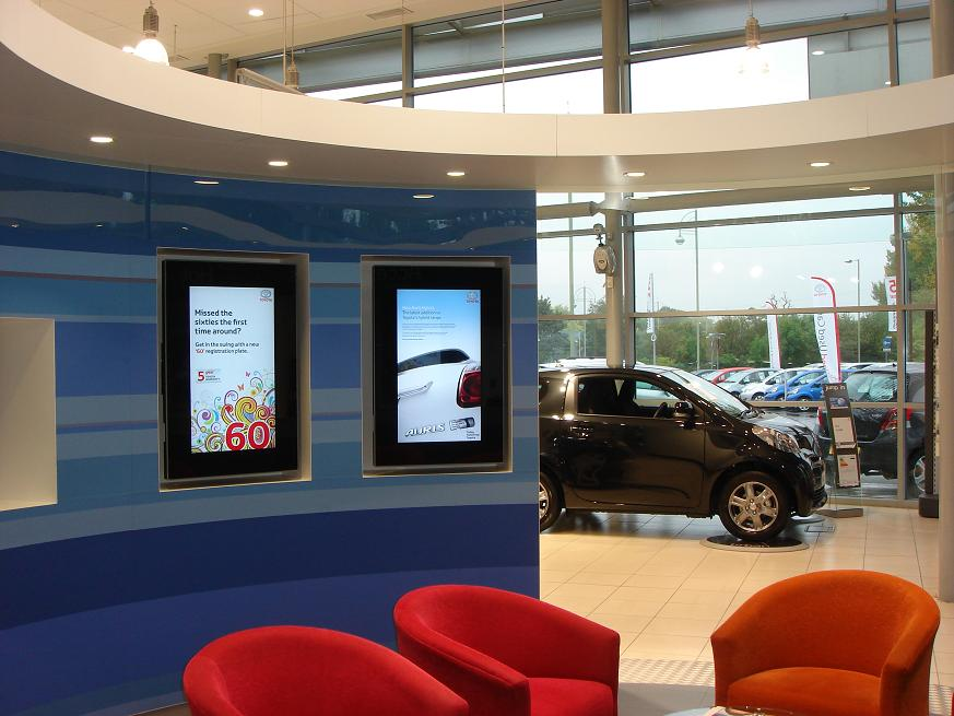 "two 32"" Digital Advertising display screens in automotive showroom"