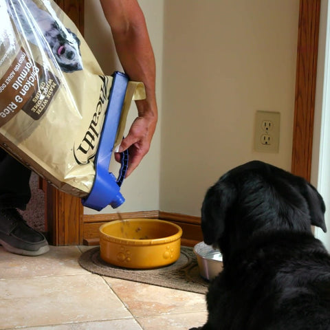 pouring bag of dog food into bowl using handle-it bag clip