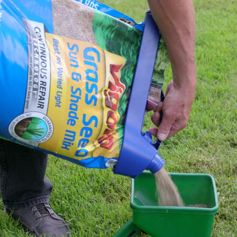 pouring bag of grass seed into spreader using handle-it bag clip