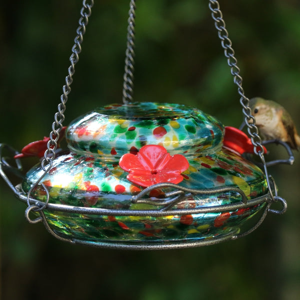 hummingbird feeding from Nature's Way hand blown glass garden hummingbird feeder in ocean sunset colors, red, yellow, green and red speckled hand blown glass