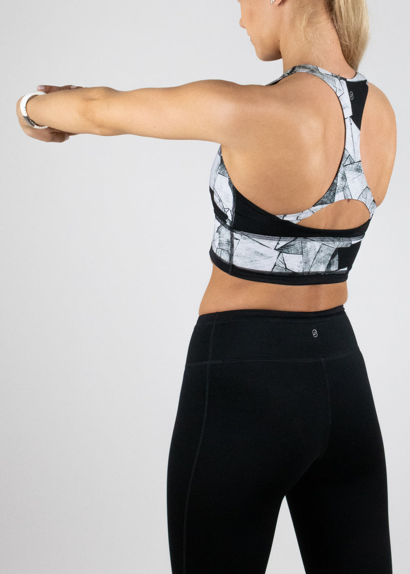 Saare crop top in the matt black and white blkgrain print with racer back and contrast panels from Susimust SS19 blkgrain collection - side back view of the model wearing the crop top and stretching her arms
