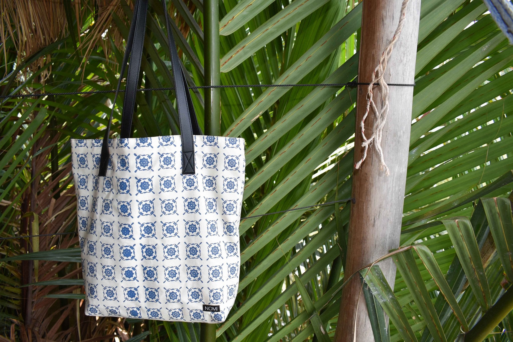 white cotton large tote with navy moroccan tile print, hanging from a wire via black straps and in front of tropical palm leaves