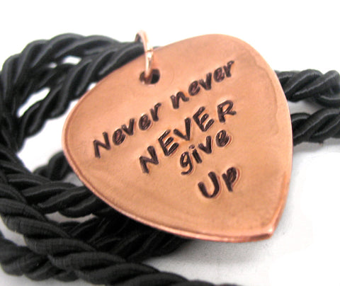 Never, never, never give up.  Hand Stamped Copper Guitar Pick Pendant, Winston Churchill inspired