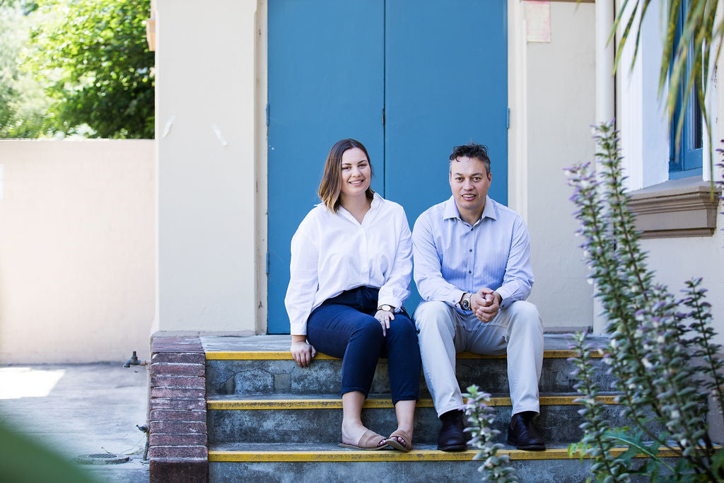 Gordon and Amy Melsom sitting on steps, in front of blue doors