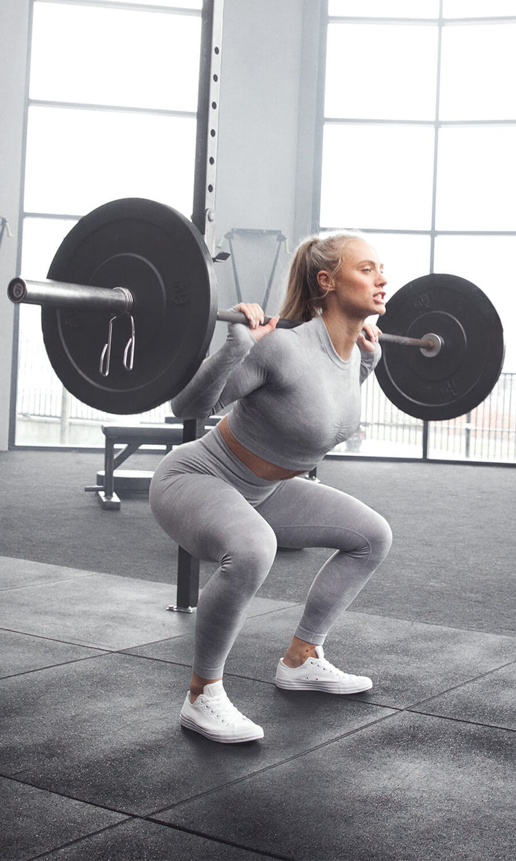 Women using a squat rack in a bright naturally lit gym wearing the new lilac grey Camo collection.