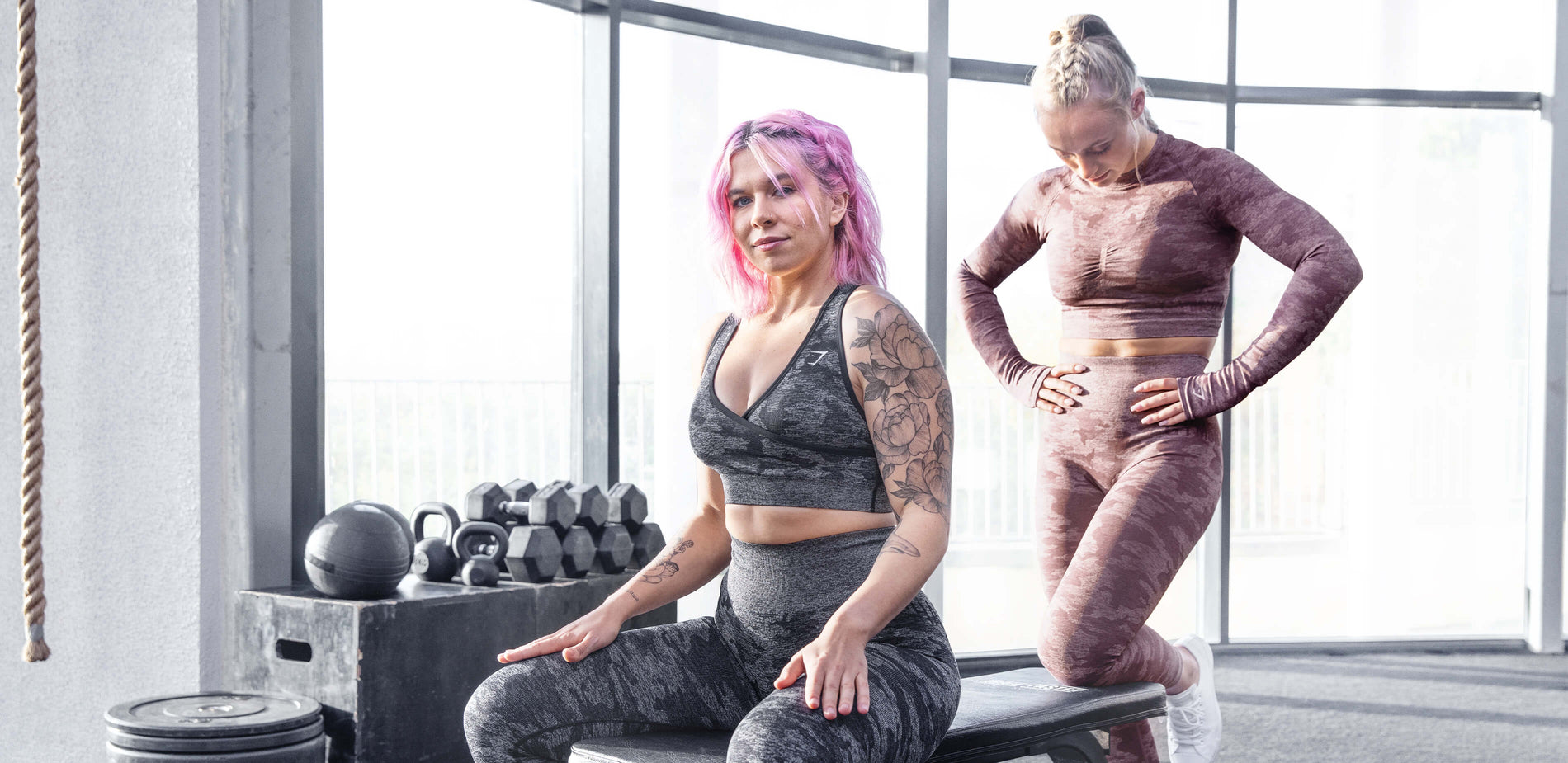 Two Gymshark models resting and posing in between sets. Decorated in the new berry red camo and the original black camo. Set in a well-lit gym with natural light.