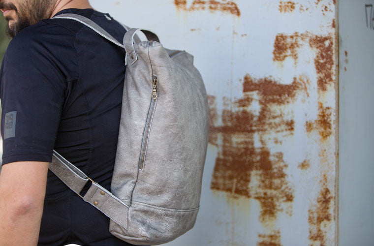 The Minos backpack in grey leather on the back by milloo