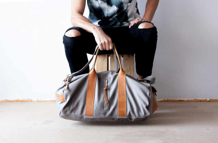 The Nestor duffel bag in grey leather hanging by milloo