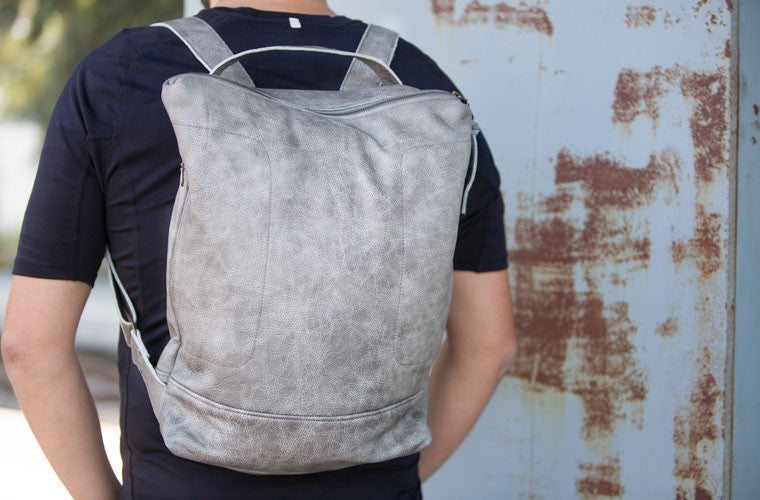 The Minos backpack in grey leather carrying by milloo