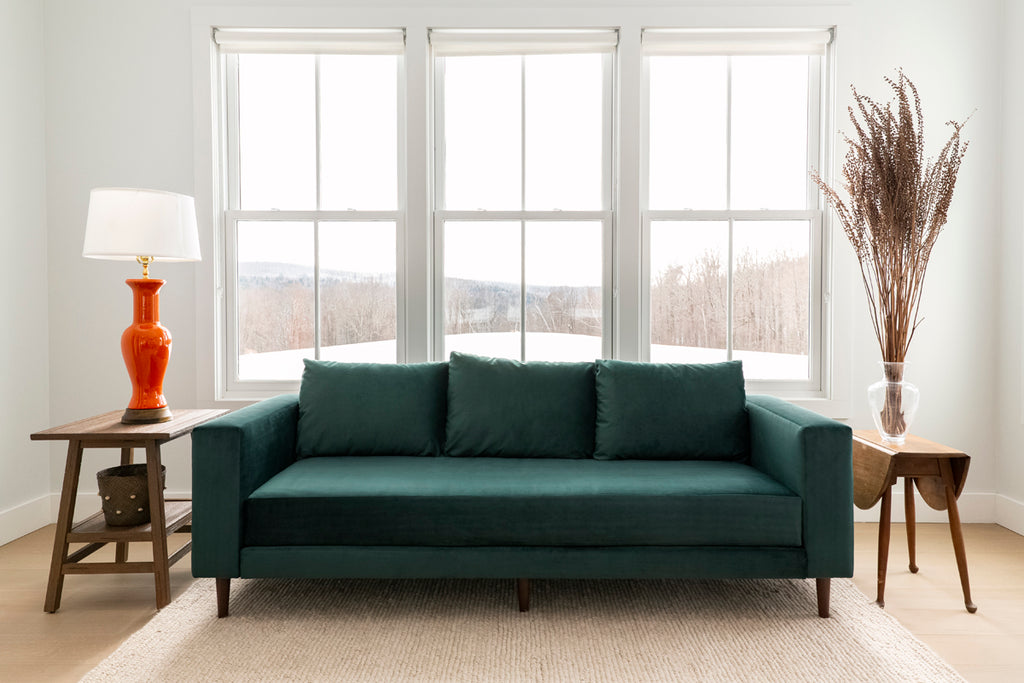 Green Sabai sofa made from sustainable materials in front of a large window