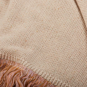 Flecked knit throw in hints of seasonal shades with parchment base. Finished with a fringe trim on all sides.