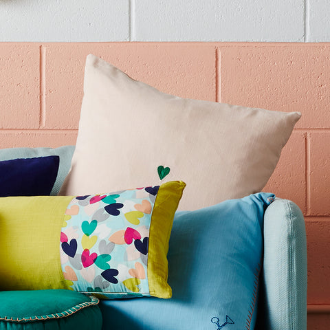 An emerald embroidered love heart punctuates this blush textured cotton cushion