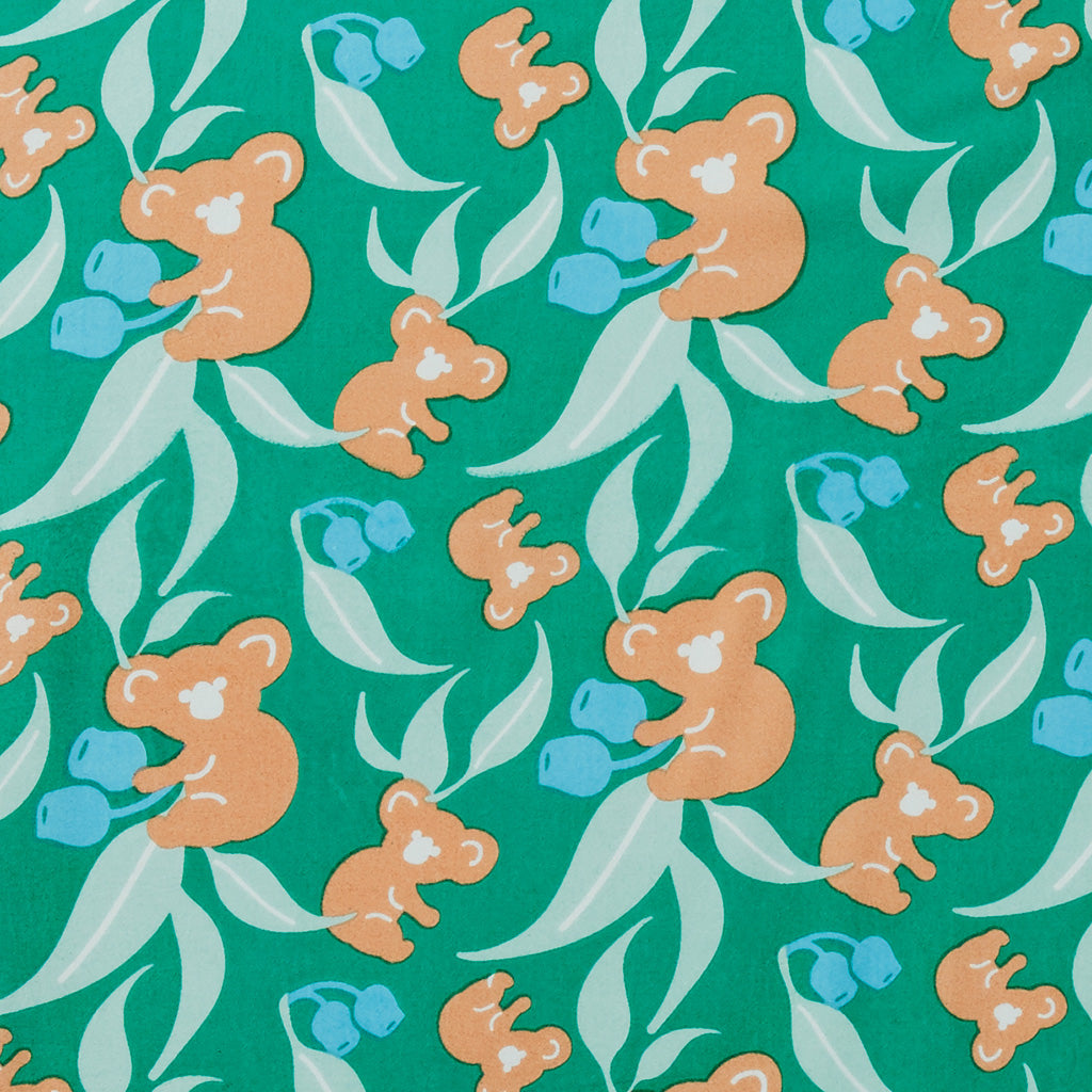 Australian-inspired pattern of koalas eucalyptus leaves and gum nuts adorn this hand printed fitted cot sheet in summery hues of turquoise emerald jade and coral
