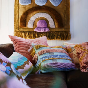 Bisti Woven Cushion - In new season colours, 70s vibe and texture. Overlapping thick lines of taffy, cornflower, terracotta and tan woven and looped to create this cushion. Finished with a playful fringe edging and aloe cotton reverse.