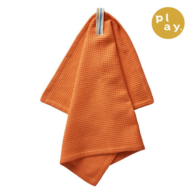 Calma Tea Towel in tangerine, with a waffle texture and printed loop